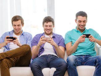 smilende mannlige venner med smarttelefoner hjemme