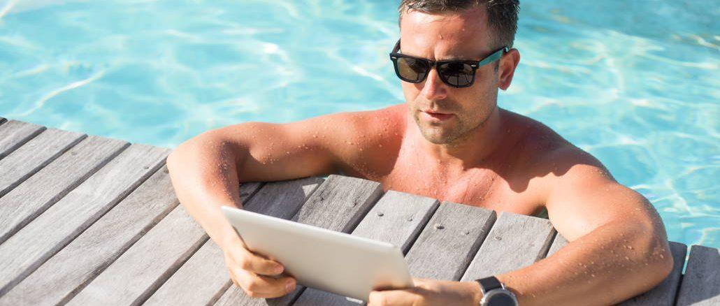 mann i et svømmebasseng med et nettbrett