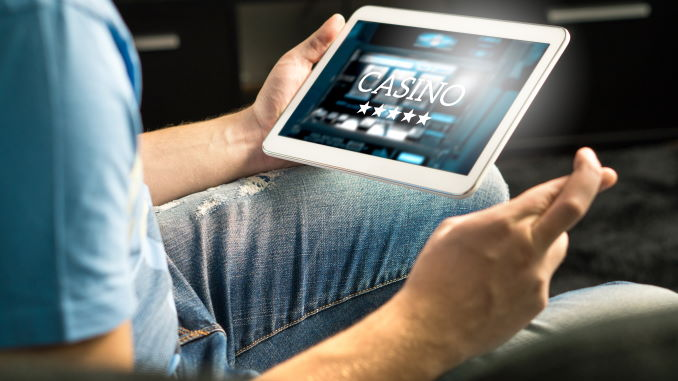 Spent mann som spiller i et nettcasino med nettbrett, fingrene krysset