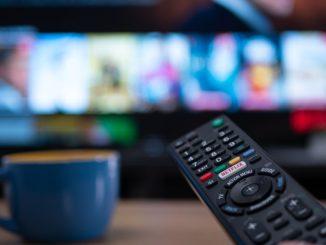 Netflix fjernkontroll foran en uskarp skjerm
