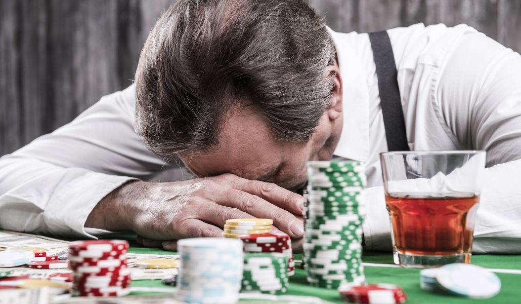 Deprimert mann med alkohol og poker sjetonger
